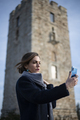 Business woman taking selfie in front of a stone tower - PhotoDune Item for Sale