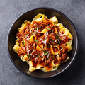 Pasta pappardelle with beef ragout sauce in black bowl. Grey background. Close up. Top view. - PhotoDune Item for Sale