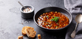 Bean soup in a black bowl. Black background. Copy space. - PhotoDune Item for Sale