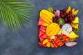 Tropical fruits assortment on a plate. Grey background. Copy space. Top view. - PhotoDune Item for Sale