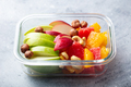Fruits salad and nuts in a glass container. Healthy eating. Grey background. Close up. - PhotoDune Item for Sale