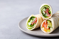 Wrap sandwich, roll with fish salmon and vegetables. Grey background. Copy space. Close up. - PhotoDune Item for Sale