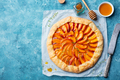 Peach galette, pie, cake with cream on blue background. Top view. Copy space. - PhotoDune Item for Sale