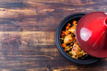 Tagine with cooked chicken and vegetables. Wooden background. Copy space. Top view. - PhotoDune Item for Sale
