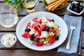 Greek salad. Fresh vegetables, feta cheese and black olives with white wine. Close up. - PhotoDune Item for Sale