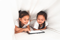 Two beautiful little sisters lying in the bed and look at the screen of a tablet, smart technology - PhotoDune Item for Sale