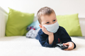 Unhappy child wearing respiratory mask as prevention against the Coronavirus Covid-19 - PhotoDune Item for Sale