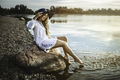 Smiling girl sitting on a rock by the lake in a white dress. Summer season. - PhotoDune Item for Sale