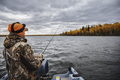 A man fishing at the lake. Fishing from a boat autumn season. - PhotoDune Item for Sale