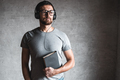 Portrait stylish bearded man dressed in grey casual t-shirt listening audio book with his earphones - PhotoDune Item for Sale