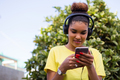Pretty young black african american woman listening to music with a headphone outdoor - PhotoDune Item for Sale