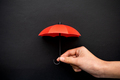 Hand hold a small red umbrella for protection concept - PhotoDune Item for Sale