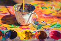 Detail view of messy painting colours and painter's cup with paintbrush on colorful canvas - PhotoDune Item for Sale