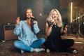Two girlfriends sing in karaoke while sitting on the floor - PhotoDune Item for Sale