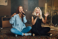 Two young woman sitting singing a duet - PhotoDune Item for Sale