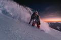 night skating snowboarder brakes spraying snow on freeride slope under starry sky and sunset light - PhotoDune Item for Sale