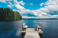 Two wooden chairs bench on a wood pier overlooking a blue lake water with green forest and cloud sky - PhotoDune Item for Sale