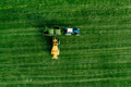 Aerial view of green grass harvest field with tractor moving hay bale - PhotoDune Item for Sale