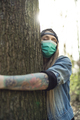 Casual Woman Hugging Tree in Park Wearing Face Protection Mask Against Coronavirus - PhotoDune Item for Sale