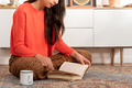 Young woman sitting on carpet and reading book at home - PhotoDune Item for Sale
