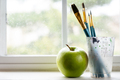 Paint brushes with a green apple next to window - PhotoDune Item for Sale