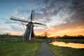 beautiful sunrise over windmill by cycling path - PhotoDune Item for Sale