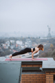 Woman practicing yoga on the mat on the roof and doing yoga exercises - PhotoDune Item for Sale
