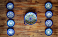 Detail of painted ornate pottery plates on wooden textured table in vintage style - PhotoDune Item for Sale
