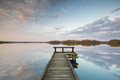 wooden pier on big lake with sky reflected - PhotoDune Item for Sale
