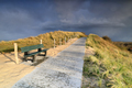 cozy bench by path up hill and stormy sky - PhotoDune Item for Sale