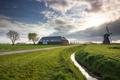 sunshine over Dutch farmland with windmill - PhotoDune Item for Sale
