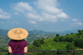 Beautiful closeup of a female leaning on the fences in Asian conical hat against mountains - PhotoDune Item for Sale