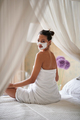 woman with facial mask sitting on the bed and enjoying at morning. - PhotoDune Item for Sale