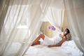 Smiling woman relaxing in  bed at home with  mask on her face.Face skin care concept. - PhotoDune Item for Sale