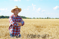 Happy looking farmer in straw hat stands at harvest ready wheat field - PhotoDune Item for Sale