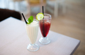 Two glasses of fresh lemonade or cocktails with ice on table in summer cafe. Shallow depth of field - PhotoDune Item for Sale