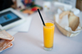 Orange drink, tablet and bread basket laid on table in cafe. Shallow depth of field - PhotoDune Item for Sale