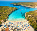 Aerial view of sandy beach with umbrellas, boats in sea bay - PhotoDune Item for Sale