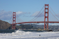 A lone fisherman fishes in the waves next to the famous Golden Gate Bridge in San Francisco. - PhotoDune Item for Sale