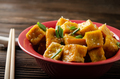 Crispy deep stir fried tofu cubes with chives in clay dish on wooden kitchen table - PhotoDune Item for Sale