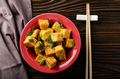 Flat lay view at crispy deep stir fried tofu cubes with chives in clay dish - PhotoDune Item for Sale