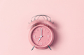 Classic pink alarm clock ringing at seven o'clock against pastel pink background - PhotoDune Item for Sale