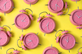 Creative layout of pink alarm clock's on pastel yellow background. Minimal concept. - PhotoDune Item for Sale