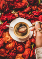 Womans hand holding spoon of espresso coffee over red flowers - PhotoDune Item for Sale