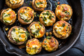 Baked champignons mushrooms, filled with cheese, parsley and roasted garlic in black bowl. - PhotoDune Item for Sale