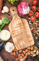 Cutting board on wooden background. Empty wood cutting board surrounded of vegetables and nuts. - PhotoDune Item for Sale