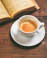 Vintage book and a cup of coffee on wooden background. Break, appointment at a cafe - PhotoDune Item for Sale