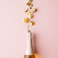 Flat lay of Celebration. Champagne bottle and golden decoration on pink background - PhotoDune Item for Sale