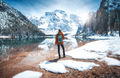 Young woman with backpack on the snowy shore of Braies lake - PhotoDune Item for Sale