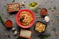 Hummus topped with chickpeas, olive oil and sun dried tomato on stone table - PhotoDune Item for Sale
